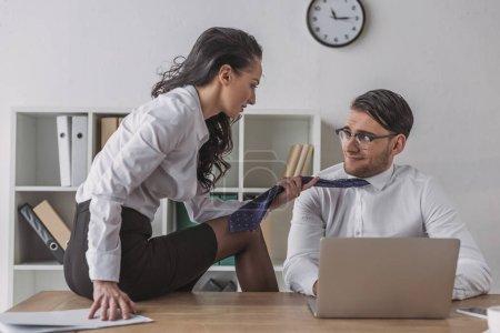 Photo pour Sexy femme d'affaires assis od bureau et touchante cravate de sourire collègue tout en le séduisant dans le bureau - image libre de droit