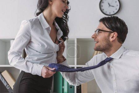Photo pour Excité homme d'affaires touchant le sein d'un collègue séduisant alors qu'elle tient sa cravate - image libre de droit