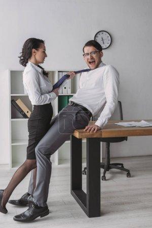 Photo pour Femme d'affaires sexy séduire collègue choqué tout en touchant sa cravate - image libre de droit