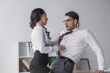 Photo pour Sexy femme d'affaires touchant cravate de choqué homme d'affaires tout en le séduisant dans le bureau - image libre de droit