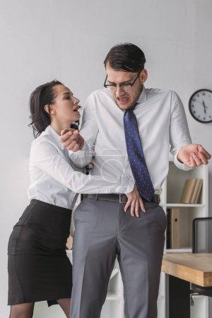 Photo pour Femme d'affaires passionnée touchant pantalon de collègue choqué tout en le séduisant dans le bureau - image libre de droit