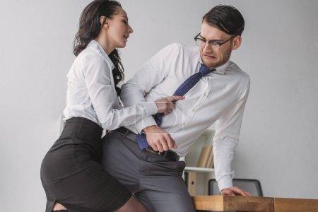 Photo pour Secrétaire passionné tenant cravate et embrassant homme d'affaires effrayé tout en le séduisant dans le bureau - image libre de droit