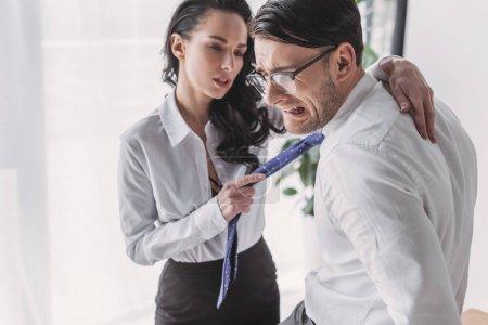 Photo pour Secrétaire sexy tenant cravate et embrassant petit ami effrayé tout en le séduisant au bureau - image libre de droit