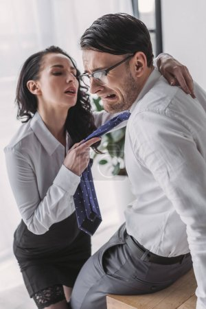 Photo pour Secrétaire sexy tenant cravate et étreignant copain effrayé tout en le séduisant au bureau - image libre de droit