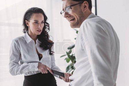 Photo pour Sexy homme d'affaires séduisant collègue en fonction tout en se touchant la ceinture - image libre de droit