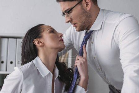 Photo pour Femme d'affaires passionnée touchant cravate de collègue confus tout en le séduisant dans le bureau - image libre de droit