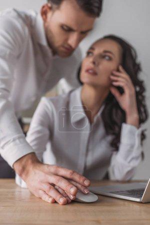 Photo pour Focalisation sélective d'un homme d'affaires toucher les mains d'une secrétaire à l'aide d'un ordinateur - image libre de droit