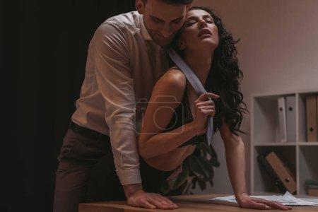 Photo pour Secrétaire séduisante en lingerie touchant cravate d'homme d'affaires sensuel avec les yeux fermés - image libre de droit