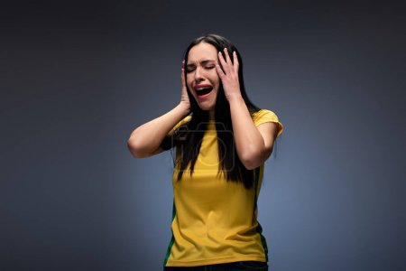 Photo for Stressed attractive young woman crying and holding head on grey - Royalty Free Image