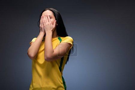 Photo pour Fan de football féminin effrayé couvrant le visage sur gris - image libre de droit