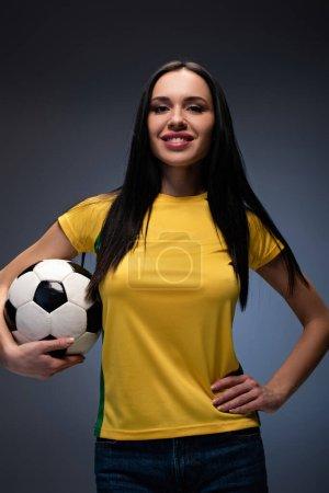 Photo pour Belle fille souriante tenant un ballon de football en gris - image libre de droit