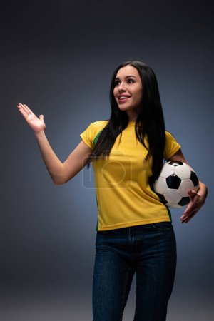 Photo for Beautiful surprised football fan holding ball on grey - Royalty Free Image