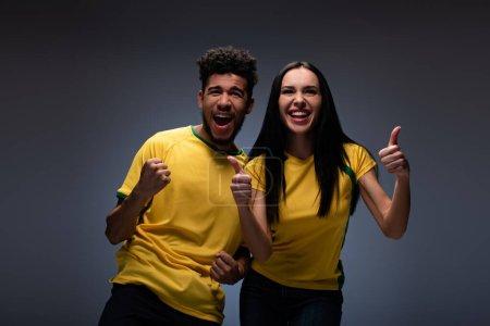Foto de Alegre pareja multiétnica de aficionados al fútbol en camisetas amarillas mostrando pulgares en gris. - Imagen libre de derechos