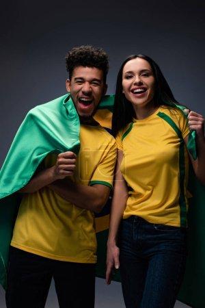 Foto de Pareja multiétnica de apasionados aficionados al fútbol con bandera descarada en gris - Imagen libre de derechos
