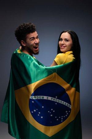Photo pour Couple multiculturel de fans de football souriants avec drapeau brésilien sur gris - image libre de droit