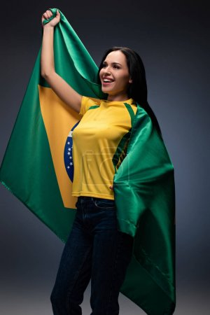 Photo for Emotional female football fan wrapped in brazilian flag on grey - Royalty Free Image