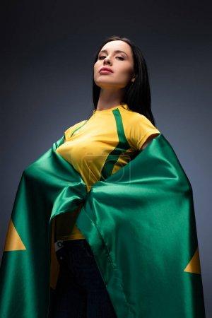 Foto de Orgulloso aficionado al fútbol femenino envuelto en bandera brasileña en gris - Imagen libre de derechos