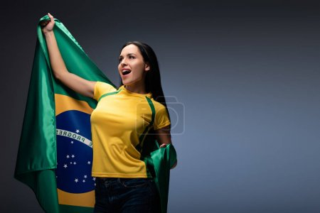 Photo for Excited female football fan holding brazilian flag on grey - Royalty Free Image