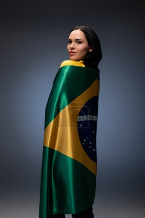 Photo for Attractive female football fan wrapped in brazilian flag on grey - Royalty Free Image