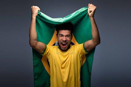 Photo pour Émotionnel afro-américain fan de football tenant drapeau brésilien sur gris - image libre de droit
