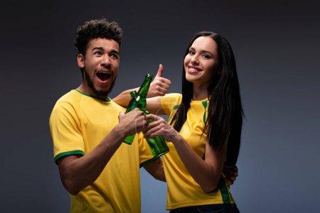 Photo pour Couple multiethnique excité de fans de football en t-shirts jaunes cliquetis avec des bouteilles de bière et montrant pouce vers le haut sur gris - image libre de droit
