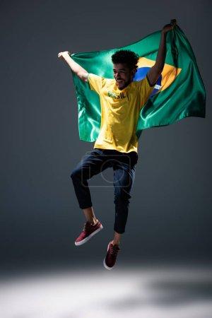 Photo pour Fan de football américain excité sauter avec le drapeau brésilien sur le gris - image libre de droit