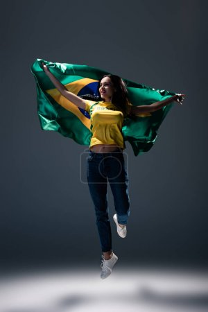 Photo for Attractive cheerful football fan jumping with brazilian flag on grey - Royalty Free Image