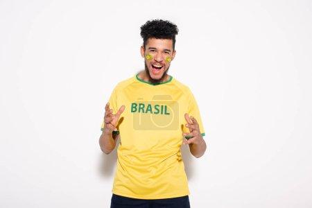 Photo pour Émotionnel fan de football afro-américain en t-shirt jaune avec signe brésilien gesticulant et criant sur gris - image libre de droit