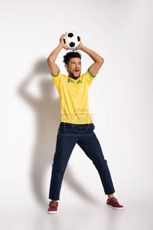Photo pour Fan de football africain américain excité en t-shirt jaune tenant le ballon sur gris - image libre de droit