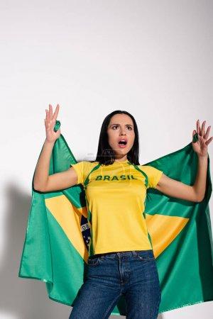 Photo for Shocked female football fan holding brazilian flag on grey - Royalty Free Image