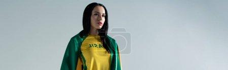 Foto de Foto panorámica de atractivas mujeres aficionadas al fútbol envuelto en bandera brasileña aislada en gris. - Imagen libre de derechos