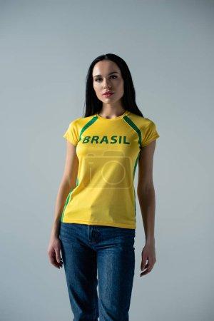 atractivo abanico de fútbol en camiseta amarilla con signo brasileño aislado en gris