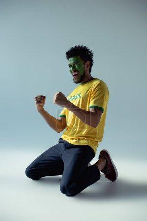 Photo pour Émotionnel afro-américain fan de football avec le visage peint comme drapeau brésilien agenouillé sur gris - image libre de droit