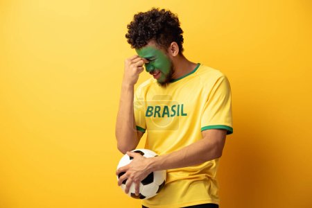 Photo for Confused african american football fan with face painted as brazilian flag holding ball on yellow - Royalty Free Image