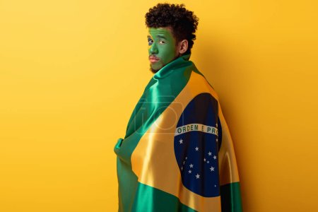 Photo for African american football fan with painted face wrapped in brazilian flag on yellow - Royalty Free Image