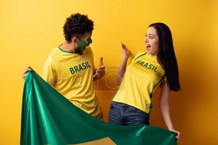 Photo pour Mâle afro-américain fan de football avec visage peint et fille heureuse geste et tenant drapeau brésilien sur jaune - image libre de droit