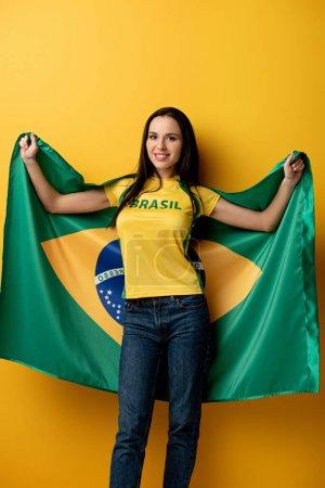 Photo pour Heureux fan de football féminin tenant drapeau brésilien sur jaune - image libre de droit