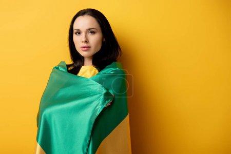 Foto de Guapa aficionada al fútbol femenina envuelta en bandera brasileña en amarillo - Imagen libre de derechos