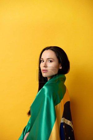 Photo pour Attrayant fan de football féminin enveloppé dans le drapeau brésilien sur jaune - image libre de droit