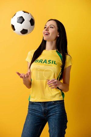 Foto de Alegre mujer aficionada al fútbol lanzando balón en amarillo - Imagen libre de derechos