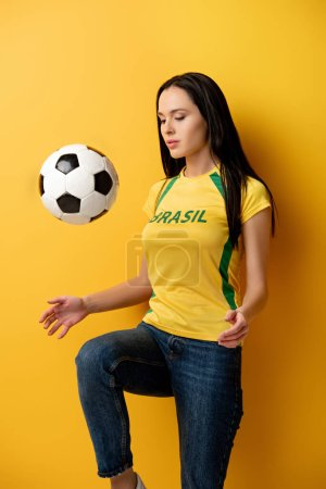 Photo for Concentrated female football fan kicking ball on yellow - Royalty Free Image