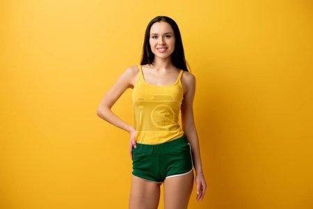 Photo pour Attrayant positive fille debout en short vert sur jaune - image libre de droit