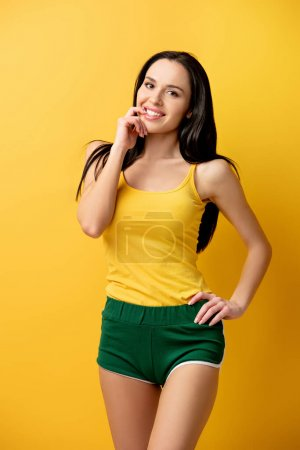 Photo for Attractive cheerful girl in green shorts on yellow - Royalty Free Image