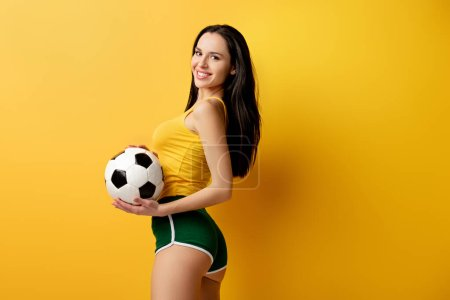 Photo for Positive female football fan in shorts holding ball on yellow - Royalty Free Image