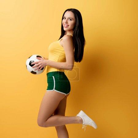 Photo pour Fan de football féminin gai en shorts tenant le ballon en jaune - image libre de droit
