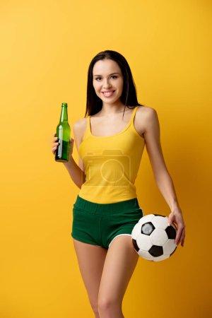Photo pour Souriant ventilateur de football féminin tenant ballon et bouteille de bière sur jaune - image libre de droit