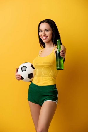 Photo for Smiling football fan holding ball and bottle of beer on yellow - Royalty Free Image
