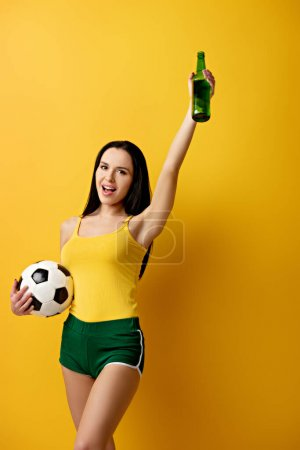 Photo for Excited female football fan holding ball and bottle of beer on yellow - Royalty Free Image