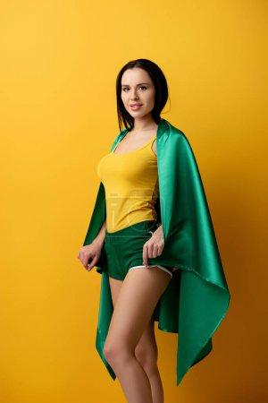 Photo pour Belle fan de football féminin en short tenant drapeau brésilien sur jaune - image libre de droit