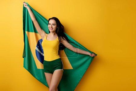Foto de Sonriente aficionada al fútbol femenino en pantalones cortos con bandera brasileña en amarillo - Imagen libre de derechos